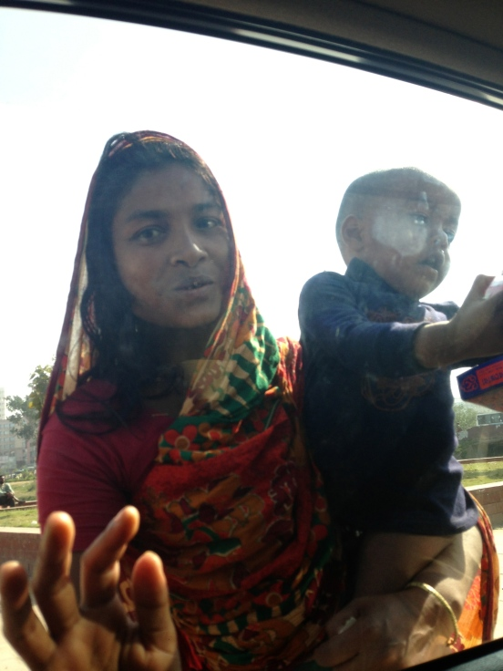 whilst being stuck on traffic in the busy and overcrowded streets of Dhaka, a young mother knocked at our car window to ask for alms